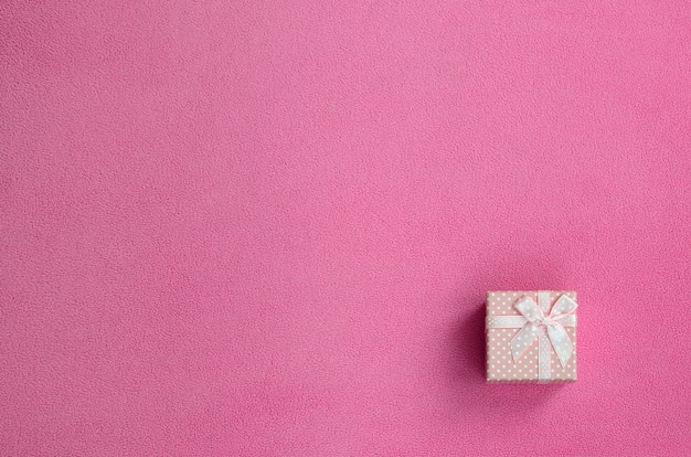 A small gift box in pink with a small bow lies on a blanket of fleece fabric