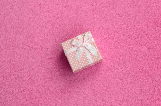 A small gift box in pink with a small bow lies on a blanket of soft and furry light pink fleece fabric