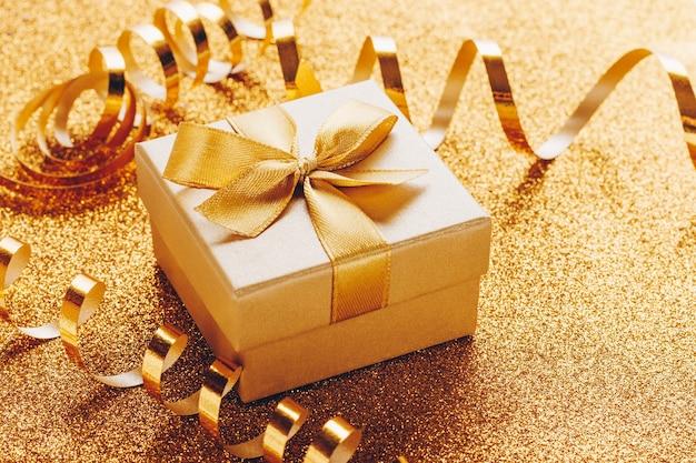 ゴールドのキラキラ背景に弓と小さなギフトボックス