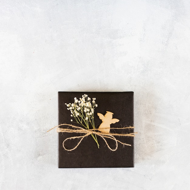 Small gift box with green branch on table