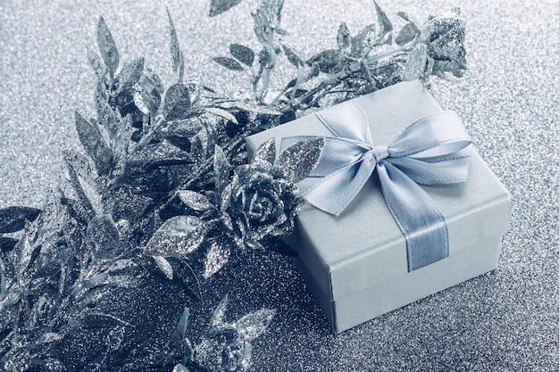 銀色のキラキラ背景にサテンの弓と人工銀の花の装飾が施された小さなギフトボックス