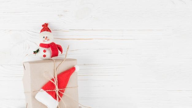 Piccola scatola regalo con pupazzo di neve sul tavolo