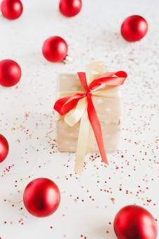 Маленькая подарочная коробка, завернутая в крафт-бумагу в горошек, елочные шары и конфетти на белом фоне