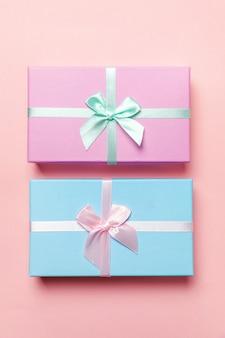 Маленькая подарочная коробка, завернутая в розовую и синюю бумагу, изолированную на розовой пастельной красочной модной