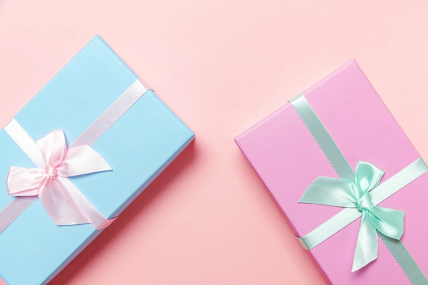 Small gift box wrapped pink and blue paper isolated on pink pastel colorful trendy