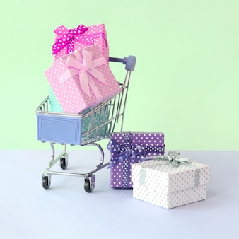 Small gift boxes of different colors with ribbons in shopping cart on a violet and blue pastel