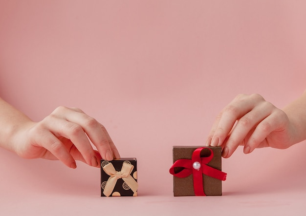 Маленькие подарочные коробки в женских руках на розовом