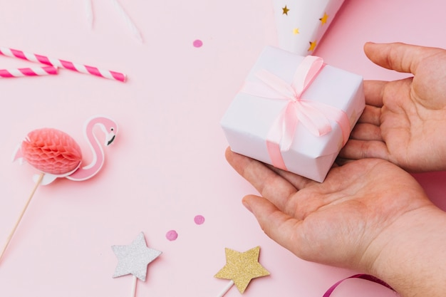 Small gift on person's hand with party props on pink background