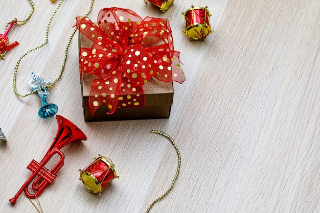 크리스마스 이브 생일 밤이나 새해 축제에 작은 장식용 음악 악기가 있는 나무 테이블에 화려한 리본 나비 넥타이가 달린 작은 선물 선물 상자.