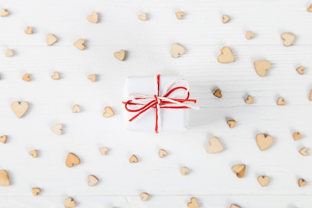 A small gift on a white table, against the of small wooden hearts, a concept for valentine's day.
