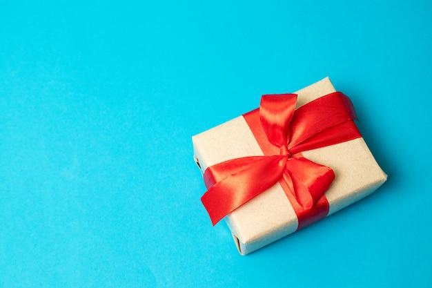 Небольшой подарок с красным бантом на красном фоне. свободное место для вашего текста.