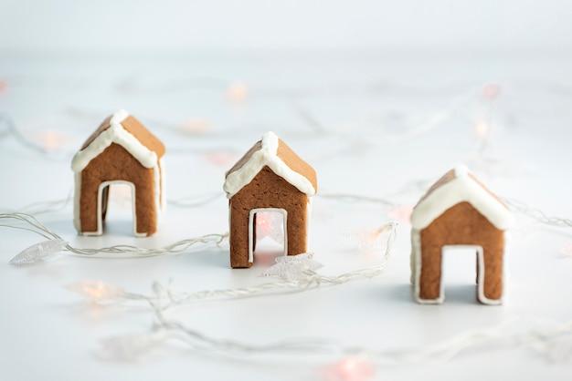 ガーランドの横にある白い背景の上のカップのための小さなジンジャーブレッドハウス。クリスマスの焼き菓子。