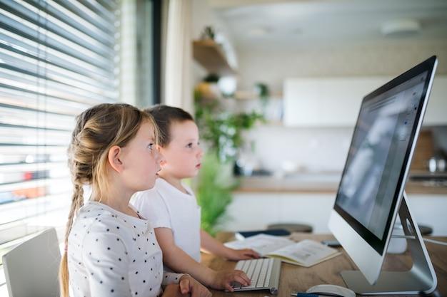 自宅の屋内でコンピューターを使用して、テーブルに座っている小さな女の子と男の子。コロナウイルスと検疫の概念。