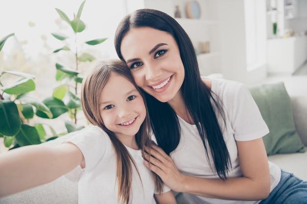 Маленькая девочка и мама обнимаются, делая селфи в домашнем доме в помещении