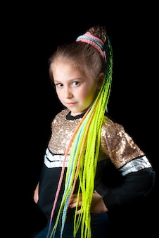 A small girl on a black background with green afro elastic bands pigtails tied in a ponytail cool