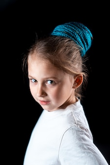 A small girl on a black background with turquoise and pink afro elastic bands, pigtails on an elastic band tied in a bun cool
