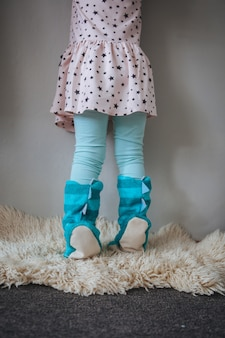 Small girl in blue home slippers standing against the wall