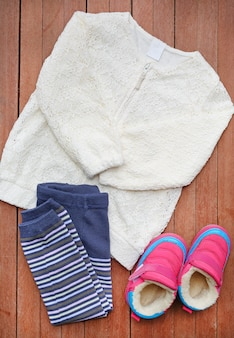 Small girl casual fashion set on wooden plank top view