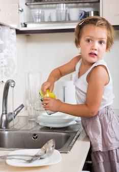 Faccende di piccola ragazza lavare i piatti