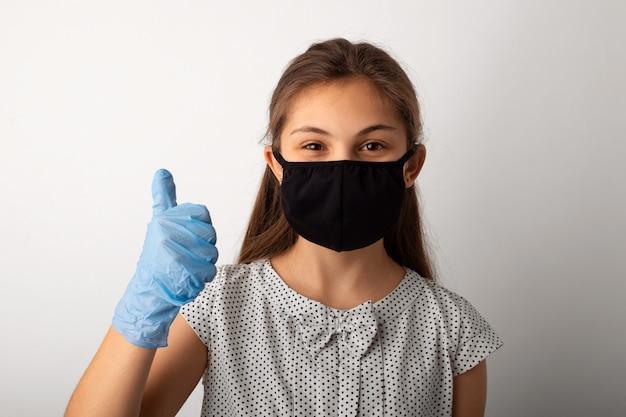 Маленькая девочка, одетая в платье и черную защитную медицинскую маску, показывает палец вверх