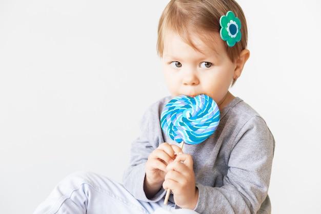 孤立したロリポップを食べる小さな女の子