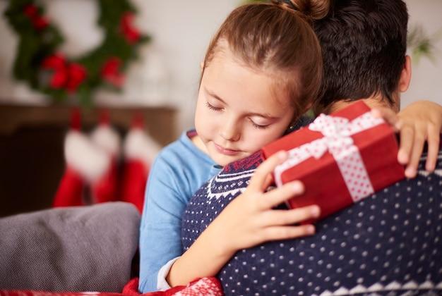 Маленькая девочка обнимает своего папу на рождество