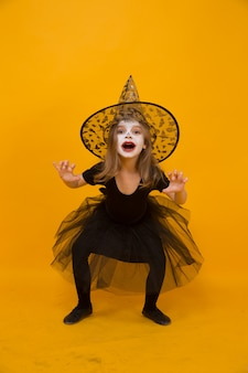 Small girl in halloween witch costume, orange surface.