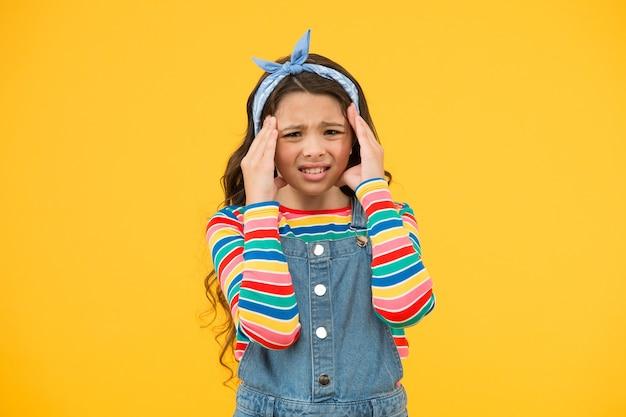 두통이 있는 작은 소녀. 레트로 소녀는 행복을 표현합니다. 여름 방학 기쁨. 작은 아이 노란색 배경. 아름다움과 패션. 행복한 어린 시절. 아프고 스트레스를 느낀다. 피곤한 어린 소녀.