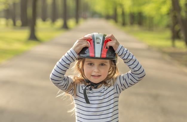 Small girl in helmet for roller outside