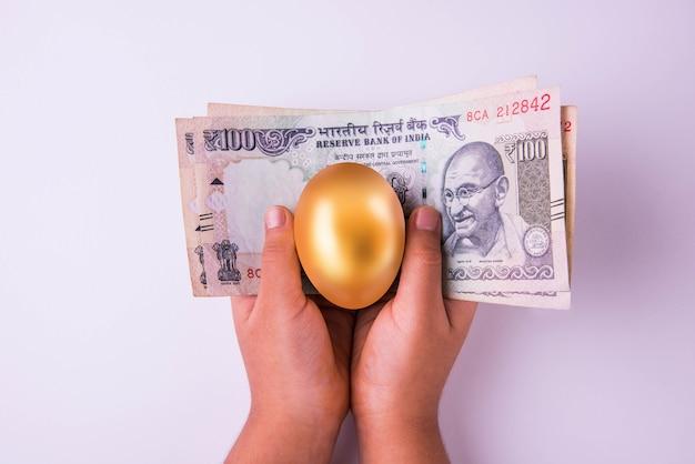 Маленькая девочка держит банкноты индийской валюты или банкноты в сто рупий и золотое яйцо над ним