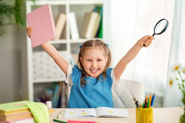 Маленькая девочка держит руки с книгой и увеличительным стеклом
