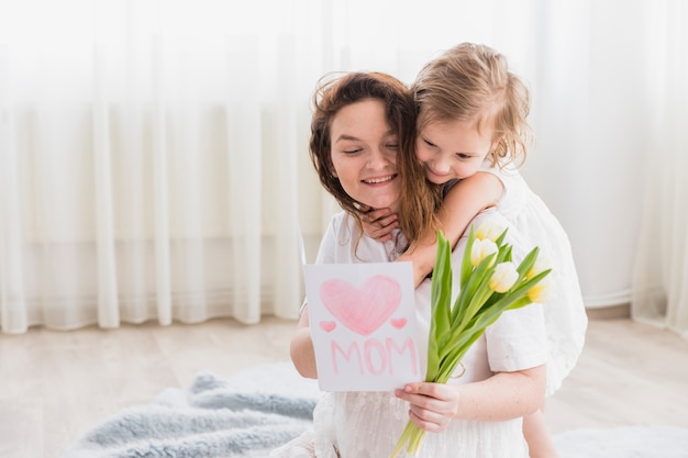 Small girl hugging her mom from back while smiling mother holding greeting card and flowers at home