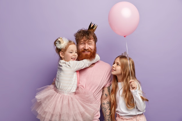 Small girl hugs red haired dad who smiles happily, glad to have two daughters, dressed in festive clothing, celebrate fathers day, hold balloon, isolated over purple wall. children, holiday, family