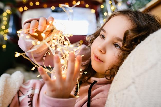 작은 소녀 조명 얼굴, 크리스마스와 새해 배경에 화환 따뜻한 노란색 조명을 들고