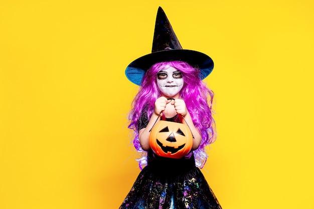 할로윈 마녀 드레스와 모자 무서 워 하 고 노란색 배경에 고립 된 얼굴을 만드는 작은 소녀. 속임수 아니면 대우.