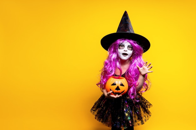ハロウィーンの魔女のドレスと帽子の小さな女の子は、黄色の背景に孤立した顔を怖がらせて作っています。トリック・オア・トリート。
