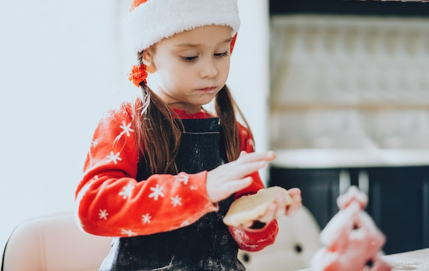 휴일 옷을 입은 작은 소녀는 밀가루가 더러워지는 크리스마스를 위해 케이크를 준비하고 있습니다.