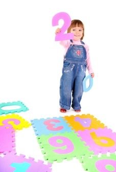 Маленькая девочка в джинсовом комбинезоне учит числа и держит два в руке над белой стеной. концепция образа жизни красивых счастливых детей