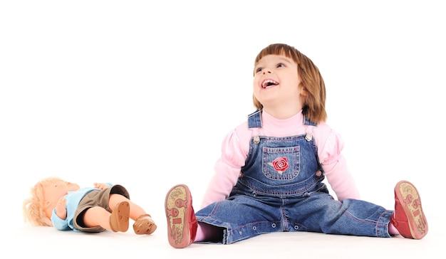 Маленькая девочка в джинсовом комбинезоне сидит на полу и улыбается