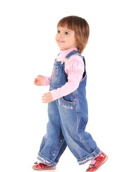 写真スタジオで白い背景の上を歩いて笑ってジーンズジャンプスーツの小さな女の子