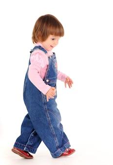 白い壁の上を歩いて笑ってジーンズジャンプスーツの小さな女の子。美しい幸せな子供たちのライフスタイルの概念