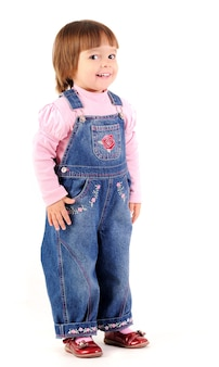 Маленькая девочка в джинсовом комбинезоне гуляет и улыбается