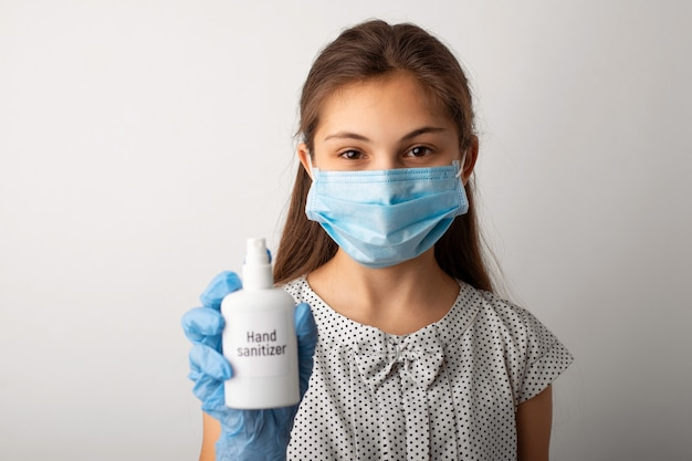 Маленькая девочка в медицинской маске и перчатках показывает дезинфицирующее средство для рук