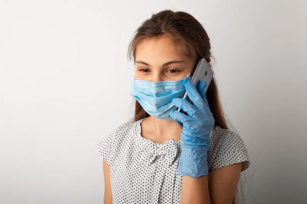 Маленькая девочка в медицинской маске разговаривает по телефону во время пандемии
