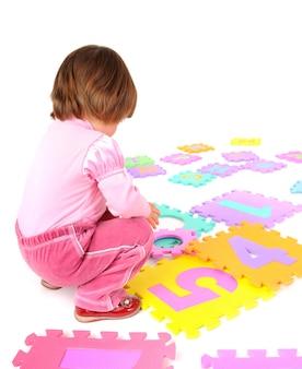 床に座って白い背景の上の数字を学ぶピンクの服を着た小さな女の子