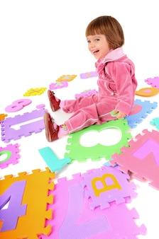 Маленькая девочка в розовой одежде сидит на полу и учит числа над белой стеной. концепция образа жизни красивых счастливых детей