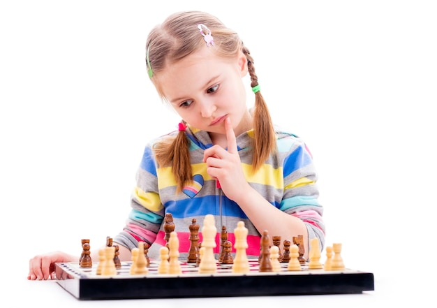 小さな女の子はチェスをするときに集中します Premium写真