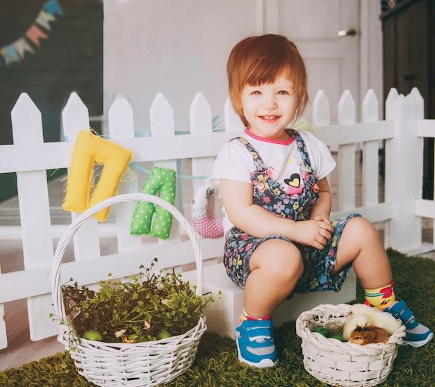 小さな女の子は笑みを浮かべてカーペット草の上に鶏と遊んでいます。