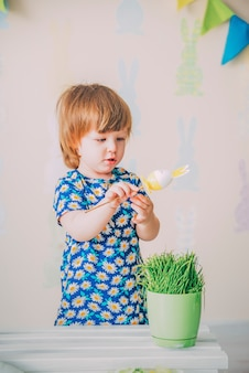 Small girl is playing with easter toy rabbit egg with grass near the wall