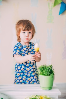 Small girl is playing with easter toy rabbit egg with grass